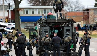 Law enforcement agents work the scene of a shooting in Bellefontaine Neighbors, Mo., on Thursday, Dec. 14, 2017.  A gunman shot two suburban St. Louis police officers in the torso before barricading himself inside a home,  but bulletproof vests saved both officers from serious injury.   (Robert Cohen/St. Louis Post-Dispatch via AP)