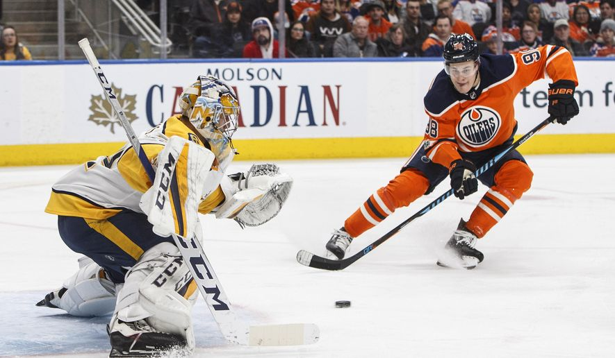 Nashville Predators goalie Juuse Saros (74) makes the save on Edmonton Oilers' Jesse Puljujarvi (98) during the second period of an NHL hockey game, Thursday, Dec. 14, 2017 in Edmonton, Alberta. (Jason Franson/The Canadian Press via AP)