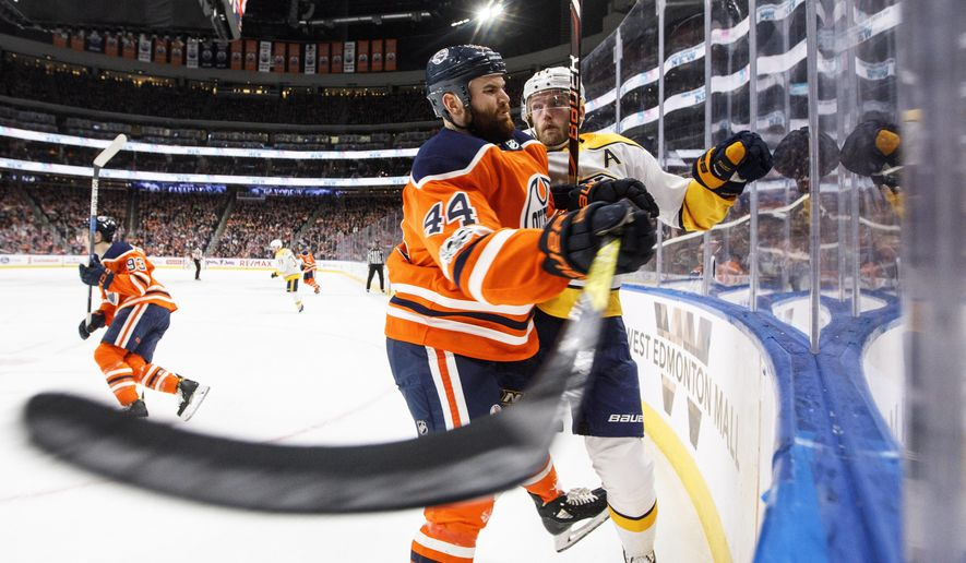 Nashville Predators' Mattias Ekholm (14) is checked by Edmonton Oilers' Zack Kassian (44) during second-period NHL hockey game action in Edmonton, Alberta, on Thursday, Dec. 14, 2017. (Jason Franson/The Canadian Press via AP)