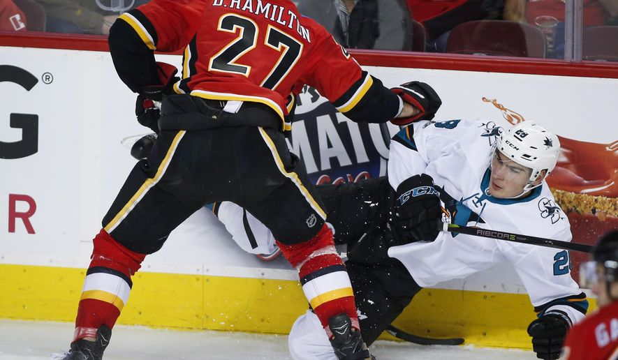 San Jose Sharks' Timo Meier, back right, from Switzerland, is checked by Calgary Flames' Dougie Hamilton during second-period NHL hockey game action in Calgary, Thursday, Dec. 14, 2017. (Jeff McIntosh/The Canadian Press via AP)