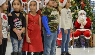 Children from Resaca Elementary School pause for applause between Christmas songs sung to members of the Winter Haven retirement community on Saturday, Dec. 16, 2017, in Brownsville, Texas. (Jason Hoekema/The Brownsville Herald via AP)