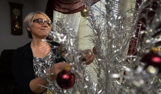 Rene Murray stands with her new vintage aluminum Christmas Tree which was an early Christmas gift from her daughter, Thursday, Dec. 14, 2017, in Great Falls, Mont. It's been Rene's Christmas dream to have an aluminum tree since she first saw one at age 10. (Rion Sanders /The Great Falls Tribune via AP)