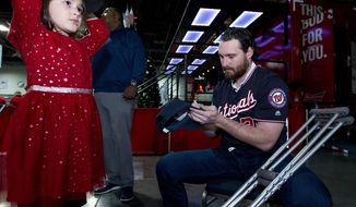 Washington Nationals Daniel Murphy signs autographs to children during the Winter Fest celebration with fans at Washington Convention center in Washington, Saturday, Dec. 16, 2017. ( AP Photo/Jose Luis Magana)
