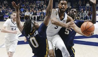 Xavier's Trevon Bluiett, center, shoots against East Tennessee State's Kanayo Obi-Rapu (0) and Peter Jurkin (5) in the first half of an NCAA college basketball game, Saturday, Dec. 16, 2017, in Cincinnati. (AP Photo/John Minchillo)