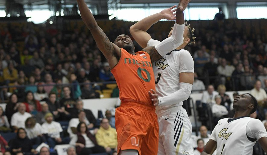 Miami guard Ja'Quan Newton (0) goes to the basket against George Washington guard Jair Bolden (3) and guard Terry Nolan Jr. (1) during the first half of an NCAA college basketball game, Saturday, Dec. 16, 2017, in Washington. (AP Photo/Nick Wass)