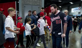 Washington Nationals Daniel Murphy, right walks with crutches during the Winter Fest celebration with fans at Washington Convention center in Washington, Saturday, Dec. 16, 2017. ( AP Photo/Jose Luis Magana) ** FILE **