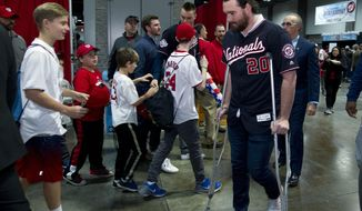 Washington Nationals Daniel Murphy, right walks with crutches during the Winter Fest celebration with fans at Washington Convention center in Washington, Saturday, Dec. 16, 2017. ( AP Photo/Jose Luis Magana)