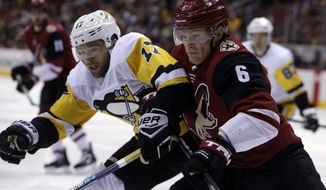 Arizona Coyotes defenseman Jakob Chychrun (6) and Pittsburgh Penguins right wing Bryan Rust battle for the puck in the first period during an NHL hockey game, Saturday, Dec. 16, 2017, in Glendale, Ariz. (AP Photo/Rick Scuteri)