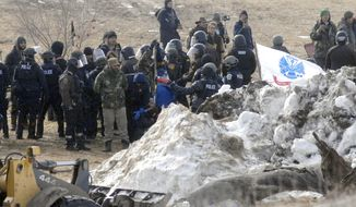 FILE - In this Feb. 23, 2017 file photo, law enforcement enters the Oceti Sakowin camp to begin arresting Dakota Access oil pipeline protesters in Morton County, near Cannon Ball, N.D. North Dakota law enforcement purchased more than $600,000 worth of body armor, tactical equipment and crowd control devices during the height of protests against the Dakota Access oil pipeline, state invoices show. (Mike McCleary/The Bismarck Tribune via AP, Pool File)