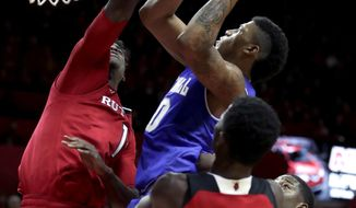 Seton Hall forward Desi Rodriguez, center, goes up for a shot against Rutgers forward Candido Sa, left, during the first half of an NCAA college basketball game, Saturday, Dec. 16, 2017, in Piscataway, N.J. Rutgers' Issa Thiam (35) and Seton Hall's Angel Delgado (31) look on during the play. (AP Photo/Julio Cortez)