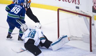 Vancouver Canucks centre Sam Gagner (89) sends the game winning goal past San Jose Sharks goalie Martin Jones (31) during overtime in an NHL hockey game in Vancouver, Friday, Dec. 15, 2017. (Jonathan Hayward/The Canadian Press via AP)