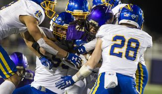 James Madison running back Taylor Woods (20) gets tackled by the South Dakota State defense during the first half of a FCS semifinal football game, Saturday, Dec. 16, 2017 in Harrisonburg, Va. (Stephen Swofford/Daily News-Record via AP)
