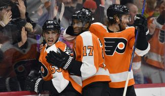 Philadelphia Flyers' Shayne Gostisbehere, left, celebrates with Wayne Simmonds, center, and Sean Couturier after Gostisbehere scored a goal during the second period of an NHL hockey game against the Dallas Stars, Saturday, Dec. 16, 2017, in Philadelphia. (AP Photo/Derik Hamilton)