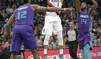 Portland Trail Blazers' CJ McCollum (3) shoots between Charlotte Hornets' Dwight Howard (12) and Michael Kidd-Gilchrist (14) during the first half of an NBA basketball game in Charlotte, N.C., Saturday, Dec. 16, 2017. (AP Photo/Chuck Burton)
