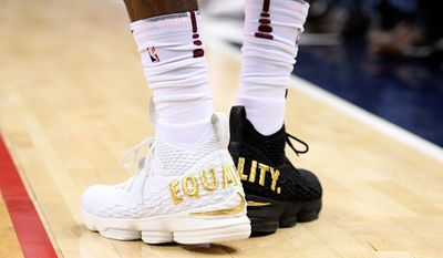 "Cleveland Cavaliers forward LeBron James played the first half on Sunday with one white shoe and one black shoe emblazoned with ""EQUALITY"" on both."