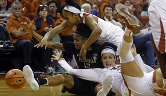 Texas guard Alecia Sutton, top, and forward Audrey-Ann Caron-Gourdreau, bottom right, fight for the ball with Florida State guard Nicki Ekhoumu, center, during the second half of an NCAA college basketball game, Sunday, Dec. 17, 2017, in Austin, Texas. (AP Photo/Michael Thomas)