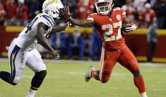 Kansas City Chiefs running back Kareem Hunt (27) runs away from Los Angeles Chargers linebacker Melvin Ingram (54) during the second half of an NFL football game in Kansas City, Mo., Saturday, Dec. 16, 2017. (AP Photo/Charlie Riedel)