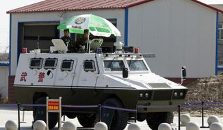 In this Nov. 3, 2017 photo, paramilitary policemen in an armored vehicle are on duty at the airport in Hotan in western China's Xinjiang region. Authorities are using detentions in political indoctrination centers and data-driven surveillance to impose a digital police state in the region of Xinjiang and its Uighurs, a 10-million strong, Turkic-speaking Muslim minority Beijing fears could be influenced by extremism. (AP Photo/Ng Han Guan)