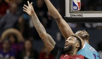 Charlotte Hornets' Dwight Howard (12) and Miami Heat's James Johnson (16) reach for the ball during the second half of an NBA basketball game in Charlotte, N.C., Friday, Dec. 15, 2017. (AP Photo/Chuck Burton)