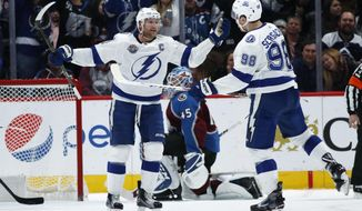 Tampa Bay Lightning center Steven Stamkos, front left, congratulates defenseman Mikhail Sergachev, front right, of Russia, after his goal against Colorado Avalanche goalie Jonathan Bernier in the third period of an NHL hockey game Saturday, Dec. 16, 2017, in Denver. The Lightning won 6-5. (AP Photo/David Zalubowski)