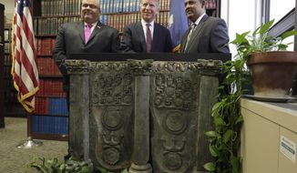 FILE - In this April 27, 2016 file photo, Homeland Security Investigations New York Special Agent in Charge Angel Melendez, left, Manhattan District Attorney Cyrus Vance Jr.,, center, and Pakistan's U.S. Deputy Chief of Mission Rizwan Saeed Sheikh, pose with an ancient Buddhist sculpture during a news conference in New York. Prosecutors returned the sculpture to the government of Pakistan after a Japanese antiquities dealer pleaded guilty to smuggling it into the U.S. (AP Photo/Richard Drew, File)