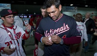 Washington Nationals Manager Dave Martinez sign autographs to children during the Winter Fest celebration with fans at Washington Convention Center in Washington, Saturday, Dec. 16, 2017. ( AP Photo/Jose Luis Magana)