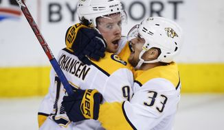 Nashville Predators' Ryan Johansen, left, celebrates his goal with teammate Viktor Arvidsson, of Sweden, during the second period of an NHL hockey game in Calgary, Alberta, Saturday, Dec. 16, 2017. (Jeff McIntosh/The Canadian Press via AP)
