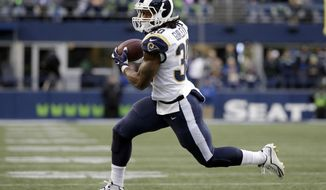 Los Angeles Rams running back Todd Gurley runs for a touchdown, his fourth of the game, after making a catch in the second half of an NFL football game against the Seattle Seahawks, Sunday, Dec. 17, 2017, in Seattle. (AP Photo/Elaine Thompson)