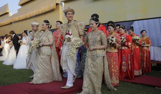 Chinese couples attend a mass wedding ceremony in Colombo, Sri Lanka, Sunday, Dec. 17, 2017. Fifty Chinese couples were married at a mass ceremony in Sri Lanka's capital to mark the 60th anniversary of diplomatic relations between the two countries and to promote the island nation as a tourist destination.(AP Photo/Eranga Jayawardena)
