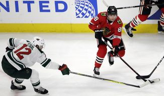 Chicago Blackhawks right wing Patrick Kane, right, looks to pass against Minnesota Wild center Eric Staal during the first period of an NHL hockey game, Sunday, Dec. 17, 2017, in Chicago. (AP Photo/Nam Y. Huh)