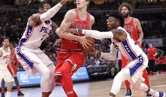 Chicago Bulls' Lauri Markkanen, center, drives between Philadelphia 76ers' Richaun Holmes, left, and Robert Covington during the first half of an NBA basketball game, Monday, Dec. 18, 2017, in Chicago. (AP Photo/Charles Rex Arbogast)