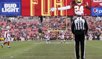 Referee Pete Morelli stands on the field prior to kick off of an NFL football game between the Arizona Cardinals and Washington Redskins, Sunday, Dec. 17, 2017, in Landover, Md. (AP Photo/Mark Tenally)
