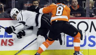 Philadelphia Flyers' Robert Hagg (8) shoves Los Angeles Kings' Anze Kopitar (11) into the boards during the second period of an NHL hockey game, Monday, Dec. 18, 2017, in Philadelphia. (AP Photo/Matt Slocum)
