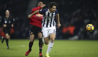 Manchester United's Marcus Rashford, left, and West Bromwich Albion's Ahmed Hegazi battle for the ball during their English Premier League soccer match at The Hawthorns, West Bromwich, England, Sunday Dec. 17, 2017. (Nick Potts/PA via AP)
