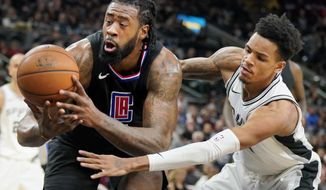 Los Angeles Clippers center DeAndre Jordan, left, loses the ball as he tangles with San Antonio Spurs' Dejounte Murray during the first half of an NBA basketball game, Monday, Dec. 18, 2017, in San Antonio. (AP Photo/Darren Abate)