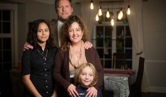 This photo taken Nov. 29, 2017, shows Des Moines school Superintendent Thomas Ahart, his wife Jami Bassman Ahart, and son Eli Bassman, 6 standing for a photo with Jennifer Galdames, 17. Galdames is living with the family after her parents were deported to Guatemala. (Zach Boyden-Holmes/The Des Moines Register via AP)