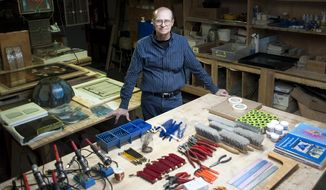 Janesville artist Richard Snyder stands in front of a table of supplies he plans to ship to Roatan, Honduras. Snyder plans to teach stained-art classes on the island starting in January. (Angela Major/The Janesville Gazette via AP)