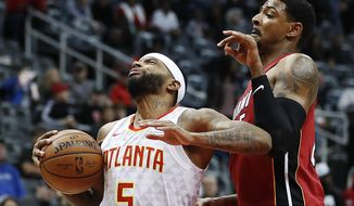 Atlanta Hawks' Malcolm Delaney, left, moves to the hoop against Miami Heat's Jordan Mickey in the first quarter of an NBA basketball game in Atlanta, Monday, Dec. 18, 2017. (AP Photo/David Goldman)
