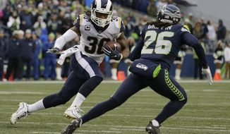 Los Angeles Rams running back Todd Gurley (30) rushes against Seattle Seahawks cornerback Shaquill Griffin (26) in the second half of an NFL football game, Sunday, Dec. 17, 2017, in Seattle. Gurley had four touchdowns and the Rams won 42-7. (AP Photo/John Froschauer)