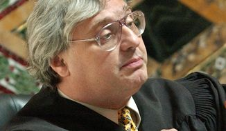 FILE - In this Sept. 22, 2003, file photo, Judge Alex Kozinski, of the 9th U.S. Circuit Court of Appeals, gestures in San Francisco. Krazinski announced his immediate retirement Monday, Dec. 18, 2017, days after women alleged he subjected them to inappropriate sexual conduct or comments. Kozinski said in a statement Monday that a battle over the accusations would not be good for the judiciary. (AP Photo/Paul Sakuma, Pool, File)
