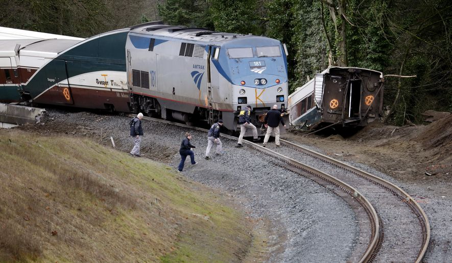 Police officials walk over tracks near a curve at the back of where an Amtrak train derailed above Interstate 5, Monday, Dec. 18, 2017, in DuPont, Wash. (AP Photo/Elaine Thompson)
