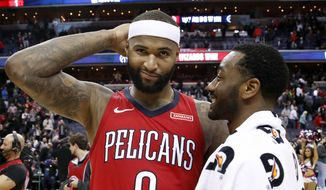 New Orleans Pelicans center DeMarcus Cousins, left, reacts as he talks with Washington Wizards guard John Wall after an NBA basketball game Tuesday, Dec. 19, 2017, in Washington. The Wizards won 116-106. (AP Photo/Alex Brandon)