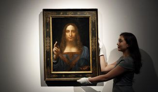 """In this Oct. 24, 2017, file photo, an employee poses with Leonardo da Vinci's """"Salvator Mundi"""" on display at Christie's auction rooms in London. An official in the United Arab Emirates says the new Louvre museum in Abu Dhabi is """"very proud"""" to have acquired a painting by Leonardo da Vinci that sold for a staggering $450 million last month.(AP Photo/Kirsty Wigglesworth, File)"""
