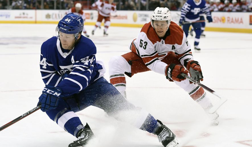 Toronto Maple Leafs defenseman Morgan Rielly (44) eludes Carolina Hurricanes left winger Jeff Skinner (53) during the first period of an NHL hockey match in Toronto, Tuesday, Dec. 19, 2017. (Nathan Denette/The Canadian Press via AP)