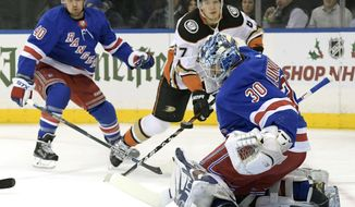 New York Rangers goalie Henrik Lundqvist (30) deflects the puck as Anaheim Ducks center Rickard Rakell (67) and Rangers right wing Michael Grabner (40) look on during the first period of an NHL hockey game, Tuesday, Dec. 19, 2017, at Madison Square Garden in New York. (AP Photo/Bill Kostroun)