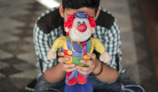A boy living in a family-style home for abandoned children poses for a photo covering his face with a clown doll in Bucharest, Romania, on Wednesday, Nov. 1, 2017. Once infamous for its orphanages, Romania is now emptying them, reuniting abandoned children with their own families or placing them in foster homes, and the goal is to shut the system down completely in a few years. (AP Photo/Vadim Ghirda)