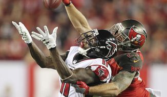 Tampa Bay Buccaneers safety Chris Conte, right, breaks up a long pass attempt to Atlanta Falcons wide receiver Julio Jones during the second half of an NFL football game in Tampa, Fla., Monday, Dec. 18, 2017. The Falcons won, 24-21. (Curtis Compton/Atlanta Journal-Constitution via AP)