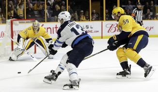 Winnipeg Jets left wing Brandon Tanev (13) scores the go-ahead goal against Nashville Predators goalie Pekka Rinne (35), of Finland, as Nashville Predators' Roman Josi (59), of Switzerland, defends in the third period of an NHL hockey game Tuesday, Dec. 19, 2017, in Nashville, Tenn. The Jets later scored an open-net goal to win 6-4. (AP Photo/Mark Humphrey)