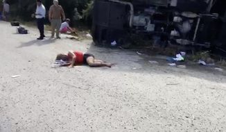 BEST QUALITY AVAILABLE - This video frame shows an injured woman lying on the road next to the overturned bus she was traveling in, in Mahagual, Quintana Roo state, Mexico, Tuesday, Dec. 19 2017. At least 12 people died when the bus carrying cruise ship passengers to Mayan ruins in eastern Mexico flipped over on a highway early Tuesday, officials said. (AP Photo/Stringer)