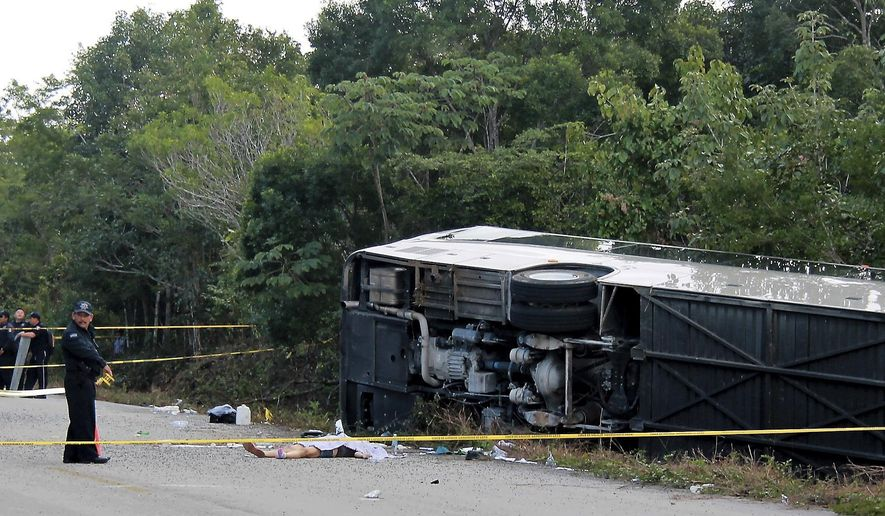 The lifeless body of a passenger lies next to an overturned bus in Mahahual, Quintana Roo state, Mexico, Tuesday, Dec. 19, 2017. The bus carrying cruise ship passengers to the Mayan ruins at Chacchoben in eastern Mexico flipped over on the highway early Tuesday. (Novedades de Quintana Roo via AP)